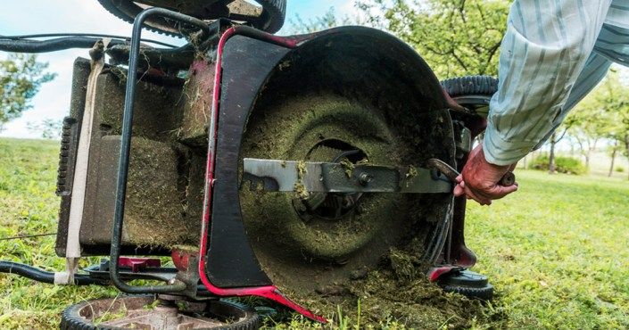 (image of grass clippings stuck to a mower)